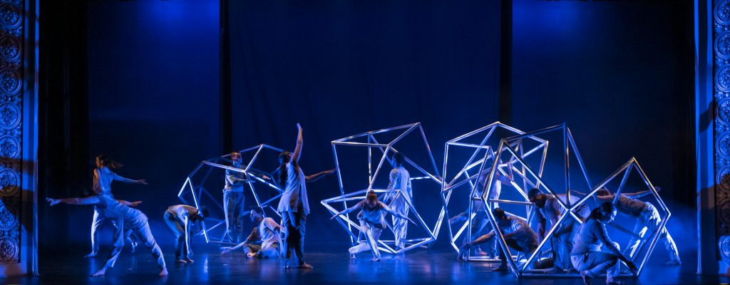 dancers perform with geometric lighted shapes