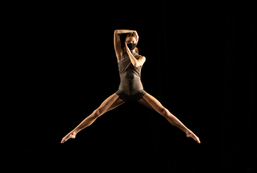 Leaping dancer wearing mask